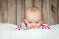 6 meses lindos de bebé en un traje del mono Imagenes de archivo