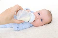 2 meses lindos de bebé que bebe de la botella Foto de archivo libre de regalías