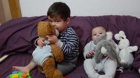 4 meses lindos del bebé en lecho púrpura con el juguete del conejito almacen de metraje de vídeo