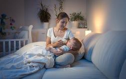 9 meses lindos del bebé que miente en revestimiento de la madre y la leche de consumo en la noche Foto de archivo