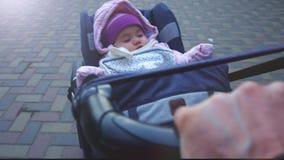 8 meses pacíficos del bebé que duerme en un cochecito al aire libre en un tiempo frío - acogedor en sombrero y guardapolvo del in almacen de video