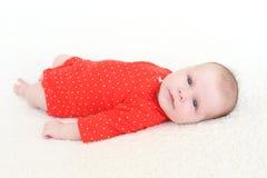 2 meses preciosos de bebé en mono rojo Imágenes de archivo libres de regalías