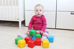 10 meses preciosos de bebé que juega bloques en casa Foto de archivo