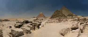 Meseta de Giza - con las tres pirámides grandes (el más oscuro cerca del centro es pequeña pirámide para una reina) y una esfinge  Imágenes de archivo libres de regalías