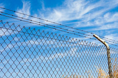Mesh fence with barbed wire. On a background of blue sky Royalty Free Stock Photography