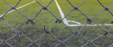 Mesh fence barrier. Front focus of the thin mesh fence barrier between us and the football field Royalty Free Stock Photo