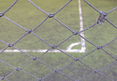 Mesh fence barrier. The thin mesh fence barrier between us and the corner football field, selective focus royalty free stock photo