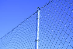 Mesh fence with a post. On clear blue sky background Stock Image