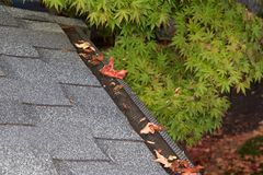 Mesh on home rain gutters keeping leaves out. Mesh guards over troughs to prevent leaves and large debris from getting into gutters. Clogged gutters less likely Stock Images