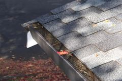 Mesh on home rain gutters keeping leaves out. Mesh guards over troughs to prevent leaves and large debris from getting into gutters. Clogged gutters less likely Stock Photo