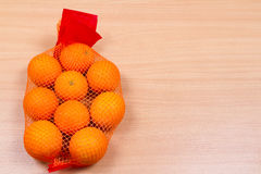 Mesh oranges from  supermarket. Lying on a wooden table Stock Image