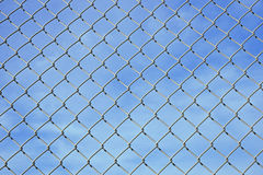Mesh wire fence and blue sky Stock Images