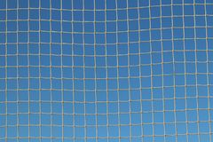 Mesh woven from a rope in the rays of clear sun against a blue sky. Transparent light burrowing. Dried out snap for catching fish. royalty free stock photo