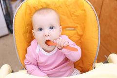 7 mesi adorabili di neonata sulla sedia del bambino in cucina Immagini Stock