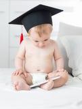 10 mesi del bambino in pannolini che indossano il cappuccio di graduazione e che usando t Immagini Stock