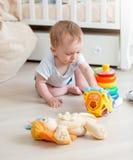 9 mesi del neonato che gioca con i giocattoli variopinti sul pavimento al liv Fotografia Stock