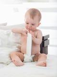 9 mesi del neonato che gioca con la compressa digitale sul letto Fotografia Stock