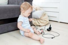 9 mesi del neonato che gioca e che tira le funi elettriche ed i cavi Bambini in pericolo Immagini Stock