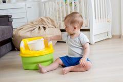 10 mesi del neonato che impara come utilizzare vaso da notte Fotografie Stock Libere da Diritti