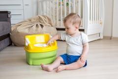 10 mesi del neonato che ottiene abituato a per mezzo del vaso da notte Immagini Stock Libere da Diritti