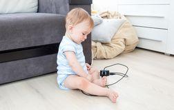 9 mesi del neonato che si siede sul pavimento al salone e che gioca con l'incavo ed i cavi elettrici Immagini Stock