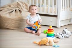 10 mesi del neonato che si siede sul pavimento di legno alla camera da letto e che gioca con i giocattoli Immagini Stock