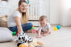 10 mesi del neonato che striscia sul pavimento e che gioca con la madre Fotografia Stock
