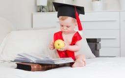 10 mesi del neonato nei libri di lettura del cappello di graduazione e mela della tenuta nella grande Fotografia Stock