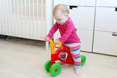 10 mesi di bambina sul camminatore del bambino a casa Immagine Stock