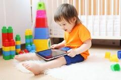 18 mesi di bambino con il computer della compressa a casa Fotografia Stock