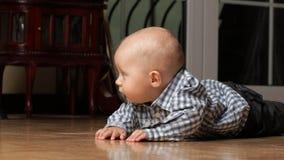 6 mesi di bambino maschio che si siede sul pavimento Immagine Stock