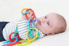 3 mesi di giochi della neonata con il giocattolo Fotografia Stock
