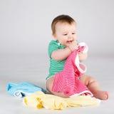 10 mesi di neonata che sceglie i vestiti Immagine Stock