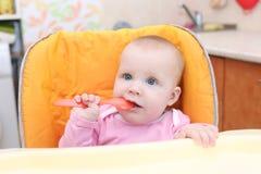 7 mesi di neonata sul seggiolone in cucina Immagine Stock
