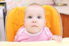 7 mesi di neonata sulla sedia del bambino Fotografia Stock