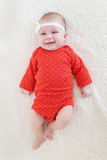 2 mesi felici di neonata in tuta rossa Fotografie Stock
