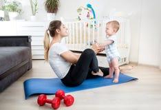 9 mesi svegli del neonato che si esercita con la giovane madre sulla stuoia di forma fisica a casa Fotografia Stock