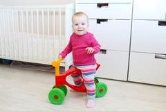 10 mesi svegli di bambina sul camminatore del bambino a casa Fotografie Stock Libere da Diritti