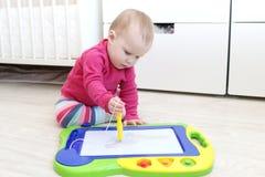 10 mesi svegli di neonata che dipinge il boa del disegno dei bambini magnetici Fotografie Stock Libere da Diritti