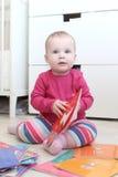 10 mesi svegli di neonata con i libri a casa Immagine Stock