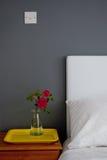 Mesita de noche con una rosa y una bandeja Fotografía de archivo libre de regalías
