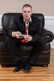 Mesmerized. A man with a TV remote control and a drink captivated by what is on television royalty free stock photo