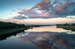 Mirror glossy surface of the Volga river reflects dramatic sunset sky. City of Tver, Russia. Royalty Free Stock Photo
