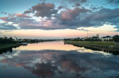 Mirror glossy surface of the Volga river reflects dramatic sunset sky. City of Tver, Russia. Royalty Free Stock Photography