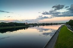 Mirror glossy surface of the Volga river reflects dramatic sunset sky. City of Tver, Russia. Stock Image