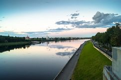 Mirror glossy surface of the Volga river reflects dramatic sunset sky. City of Tver, Russia. Stock Photo