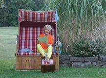 Mesmo em uma cadeira de praia de vime telhada, a mulher atrativa com a tabuleta é sempre moderna foto de stock