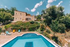 Mesonisia,罗希姆诺,克利特- 2018年8月:往别墅Krios的看法与游泳池在与迷离天空的一个晴天 库存图片