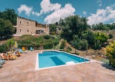 Mesonisia, Rethymno, Kreta - Augustus 2018: Mening naar villa Krios met zwembad op een zonnige dag met onduidelijk beeldhemel royalty-vrije stock afbeelding