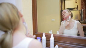 Mesotherapy在家 女孩mesorollerom处理房子的面孔在镜子前面的 股票录像